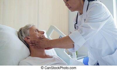 Professional female doctor examing a senior sick man