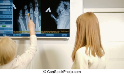 Professional female doctor reading x-ray film of brain and on the phone 4k