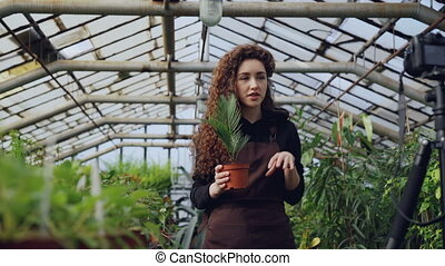 Professional female gardener is recording tutorial about...