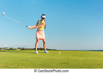 Professional female golf player smiling while swinging a driver club