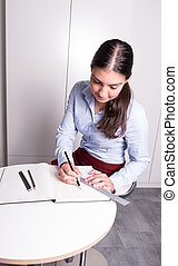 professional female is drawing in a notebook with ruler and pencil