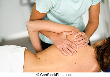 Professional female physiotherapist giving shoulder massage to a woman