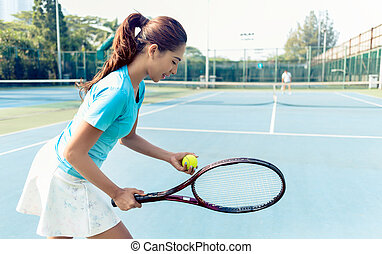 Professional female player smiling while serving during tennis match