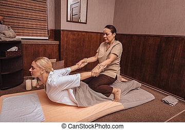Professional female Thai masseuse doing the massage
