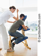 Professional female therapist giving massage to man