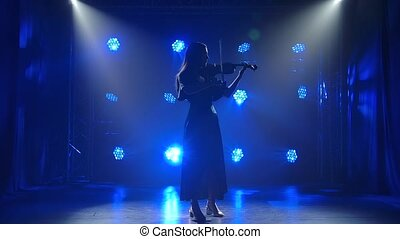 Professional female violin player having a solo. Silhouette of a woman spotted by light on black background with blue lights. Slow motion
