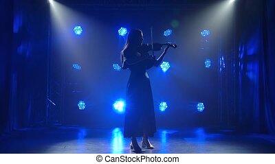 Professional female violin player having a solo. Silhouette ...