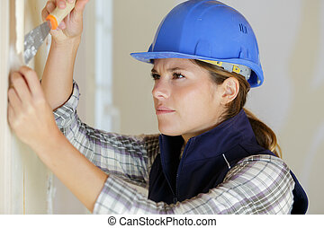 professional female worker stripping wallpaper