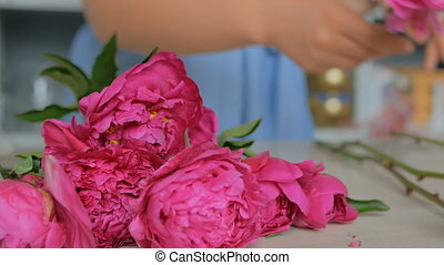 Professional floral artist sorting flowers at studio -...