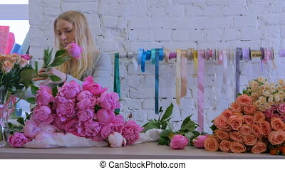Professional floral artist sorting flowers at studio -...