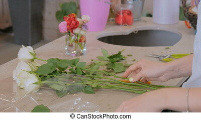 Professional floral artist working with flowers at studio -...