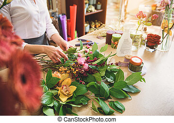 Professional florist creating masterpiece from plants - ...