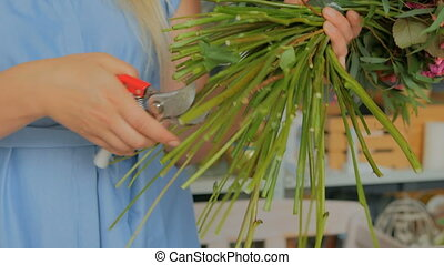 Professional florist cutting flower stems at studio -...