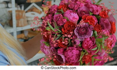 Professional florist holding and checking bouquet at studio...