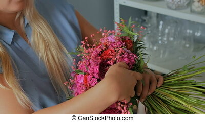 Professional florist holding and checking bouquet at studio