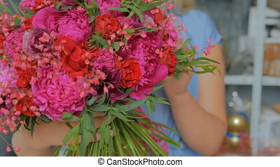 Professional florist holding and showing bouquet at studio