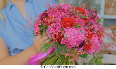 Professional florist holding and showing bouquet at studio -...