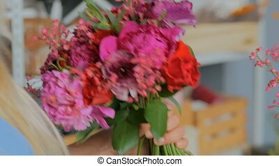 Professional florist making beautiful bouquet at flower store
