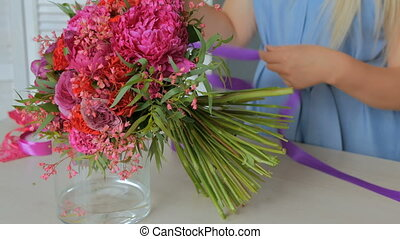 Professional florist making beautiful bouquet at flower...