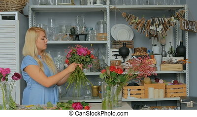 Professional florist making floral wedding composition at flower shop
