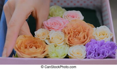 Professional florist making gift box with flowers at flower store