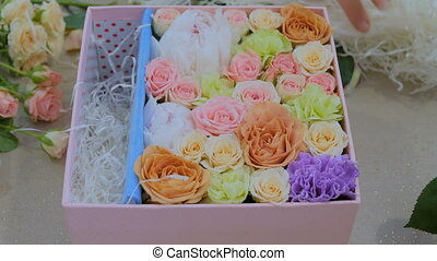 Professional florist making gift box with flowers at flower...