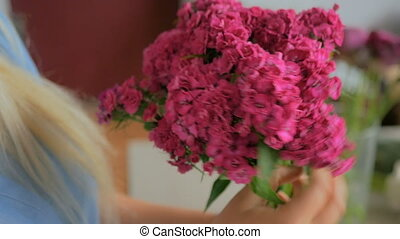 Professional florist preparing pink turkish carnation for bouquet at workshop
