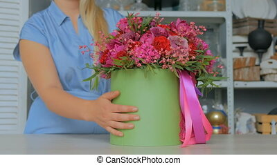Professional florist showing bouquet at studio -...
