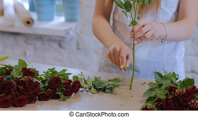 Professional florist working with flowers at studio -...