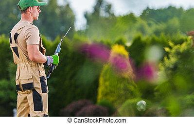 Professional Gardener with His Tools In the Backyard Garden