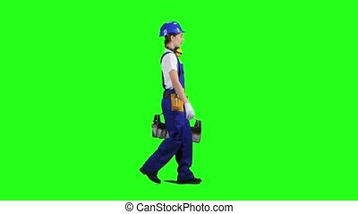 Professional girl carries a case with construction tools. Green screen. Side view