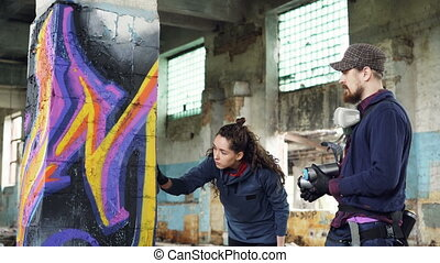 Professional graffiti artist is teaching pretty girl to...