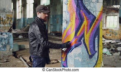 Professional graffiti painter is creating abstract image on...