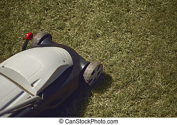 Professional grass-cutter mowing green lawn on backyard. Gardening care equipment. Sunny day, close up
