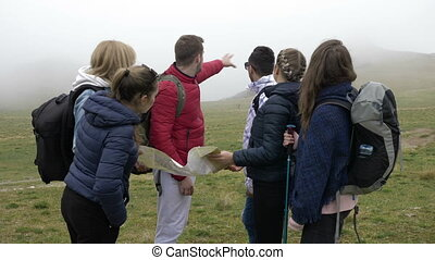 Professional guide man explaining the route to young...