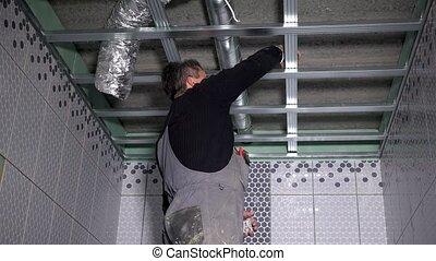 Professional guy fix ceiling profiles. Static closeup shot.