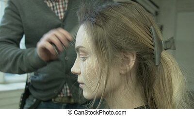 Professional Hair Dresser Used a hairdryer. Male stylist with a hairdryer. Young woman getting her hair dressed in hair salon. Hairdresser combs hair to beautiful blonde. Beauty saloon