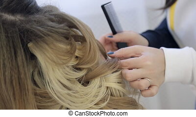 Professional hairdresser braiding clients hair on wedding hairstyle