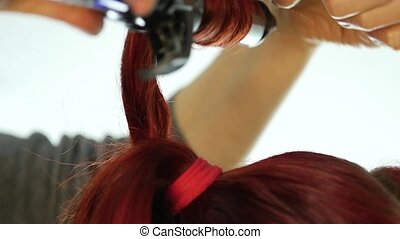 professional hairdresser make curls, uses curling rod. slow...