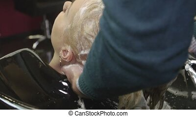Professional hairdresser rub in shampoo in hair of blonde girl in beauty saloon. Massage of head