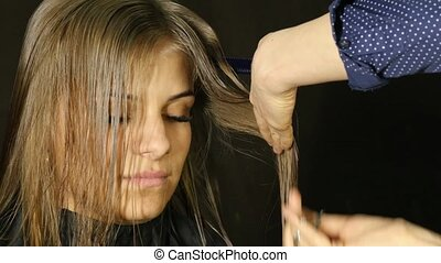 Professional hairdresser separates hair strands cutting bangs of woman client in hair salon.