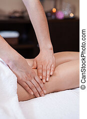 professional hand massage of woman legs. burning candles on background on table