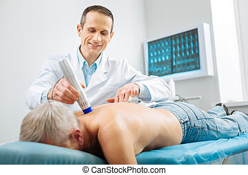 Professional handsome doctor using special device