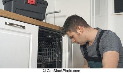 Professional handyman in overalls repairing domestic...