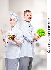 professional happy chefs in suits with a salad in their hands against the background of the kitchen