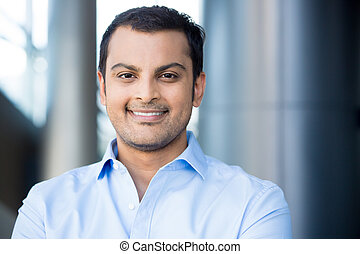 Closeup headshot portrait, happy handsome business man, smiling, in blue shirt, confident and friendly on isolated office interior background. Corporate success