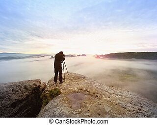 Professional hiker and photographer shooting in nature with a digital camera and a tripod