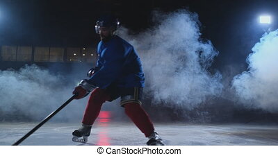 Professional hockey player with a stick accelerates on the...