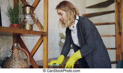 Professional housekeeper is dusting furniture with wet cloth...