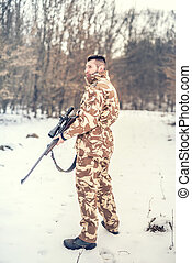 professional hunter looking for prey during winter season. War, hunting or protection concept with young sniper